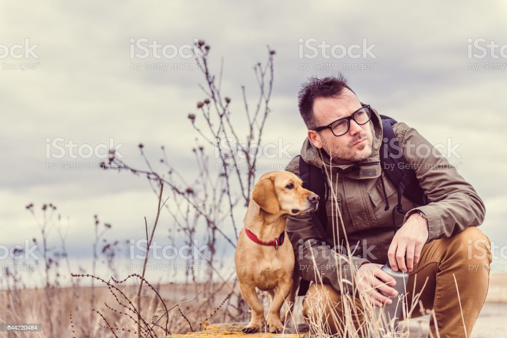 Hiker and dog resting stock photo