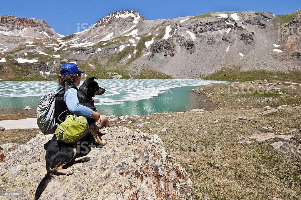 Hiker and Dog Sitting on a Rock at Ice Lake royalty-free stock photo