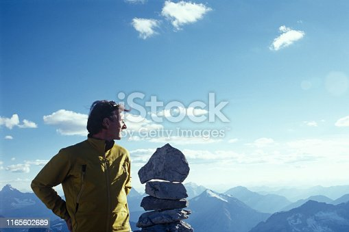 He looks off to the distant mountains from the cairn, Banff National Park, Alberta