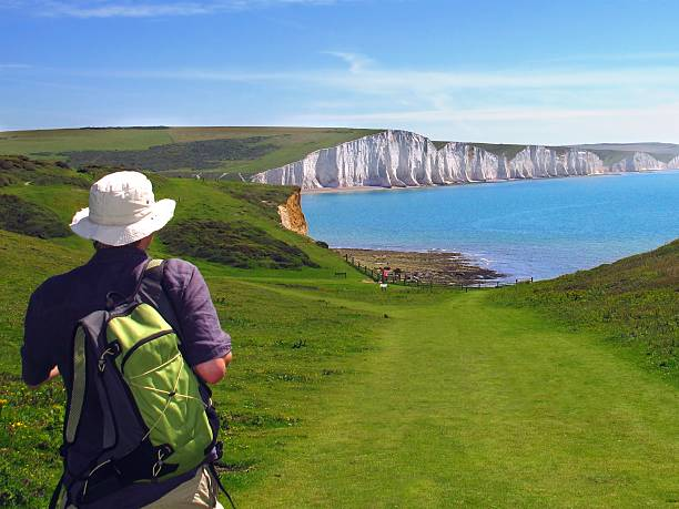 hiker and white cliffs of Seven Sisters, East Sussex, England stock photo