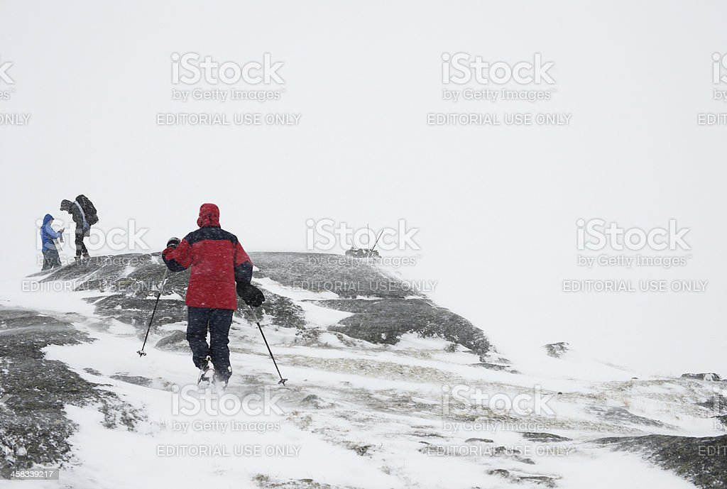 Hiker approaches mountain peak in bad weather stock photo