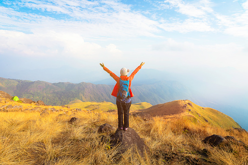 Hiker asian woman happy feeling freedom good and strong weight victorious facing on the natural mountain. Travel Concept