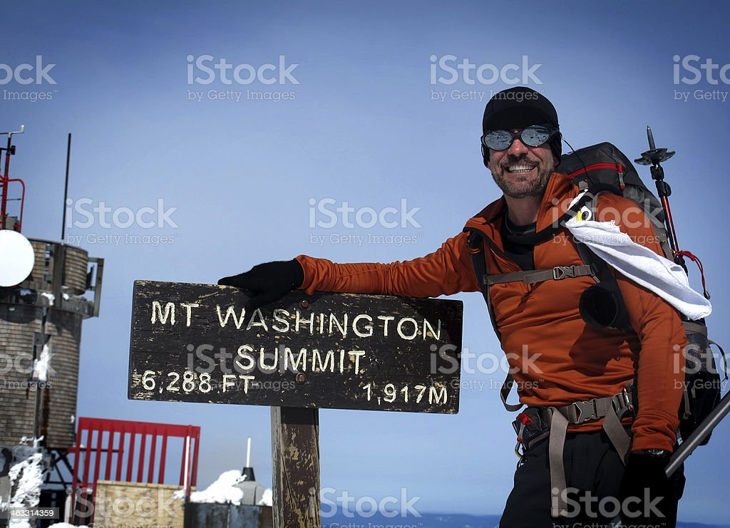 Hiker at 6288ft, taking photograph with Mt Washington summit sign  stock photo
