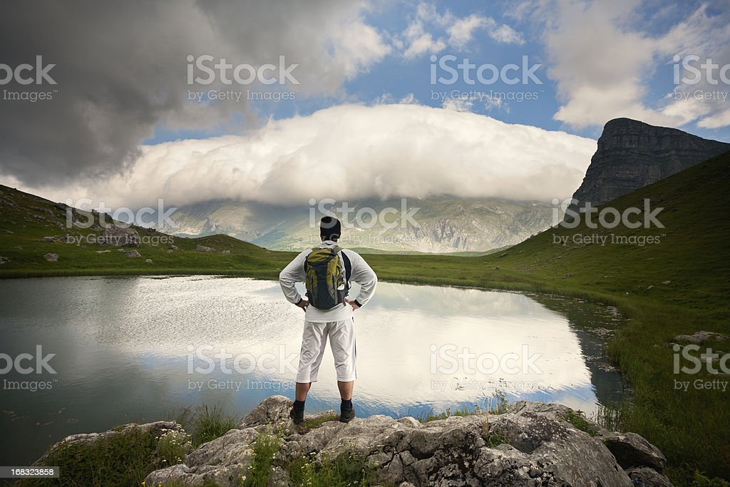 Hiker at lake surrounded by mountains royalty-free stock photo