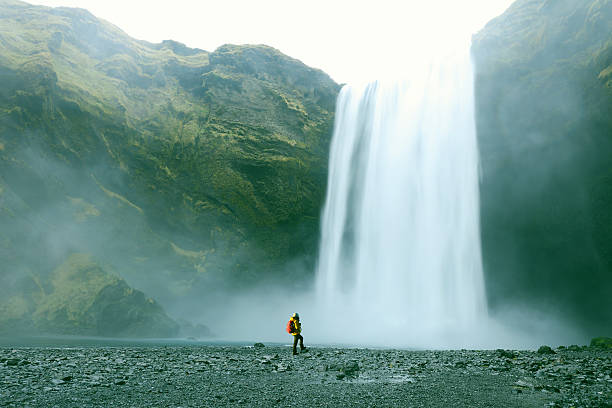 hiker at majestic skogafoss waterfall in iceland - waterfall stock photos and pictures