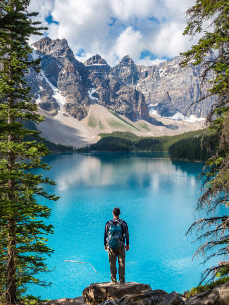 Hiker at Moraine Lake in Banff National Park, Alberta, Canada Hiker looking at view at Moraine Lake in Banff National Park, Canadian Rockies, Alberta, Canada. rocky mountains north america stock pictures, royalty-free photos & images