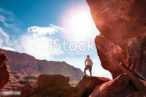 Hiker looking at mountain view from a large rock formation in Utah, in panoramic view