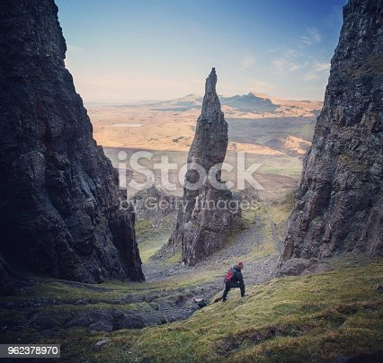 A Hiker stops on a steep path by the Needle Pinnicle at the Quirang on the Isle of Skye and contemplates the scene.
