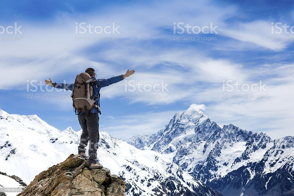 Hiker at the top of a rock with hands raised royalty-free stock photo
