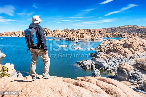 Stock photograph of a hiker with backpack looking at view at Watson Lake, Prescott, Arizona USA on a blue sky day.
