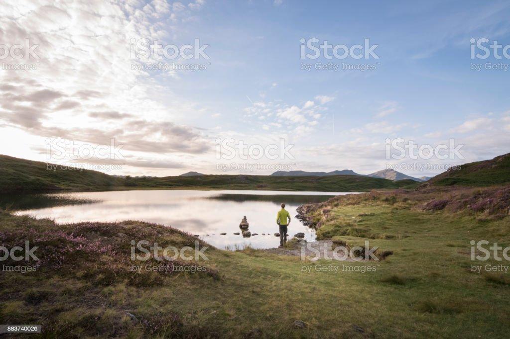 Wandelaar awing over de prachtige scène met lake district berg achtergrond en paarse Heide foto