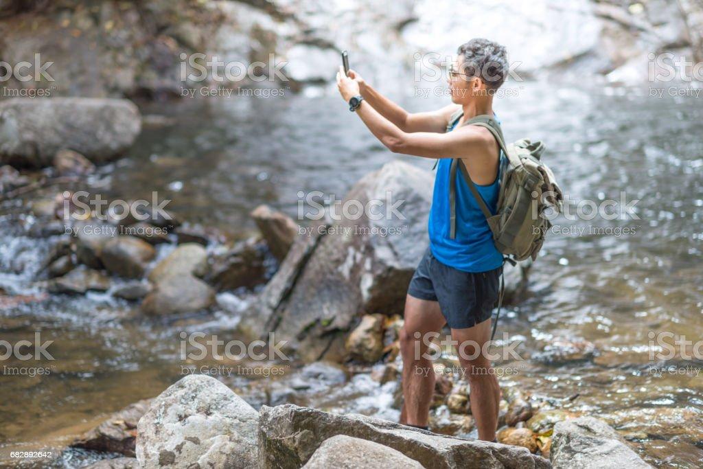 Wanderer-Rucksack mit Laptop und Handy am Wasserfall im Wald. Lizenzfreies stock-foto