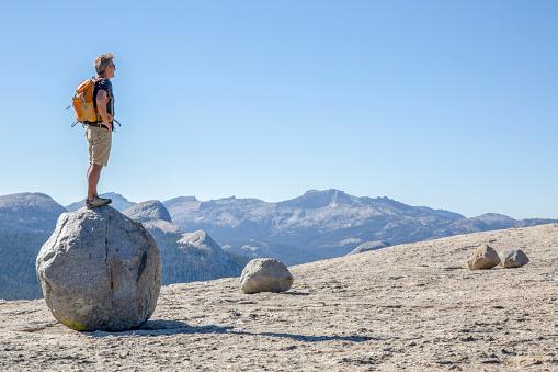 Hiker balances on a rock boulder above mountains