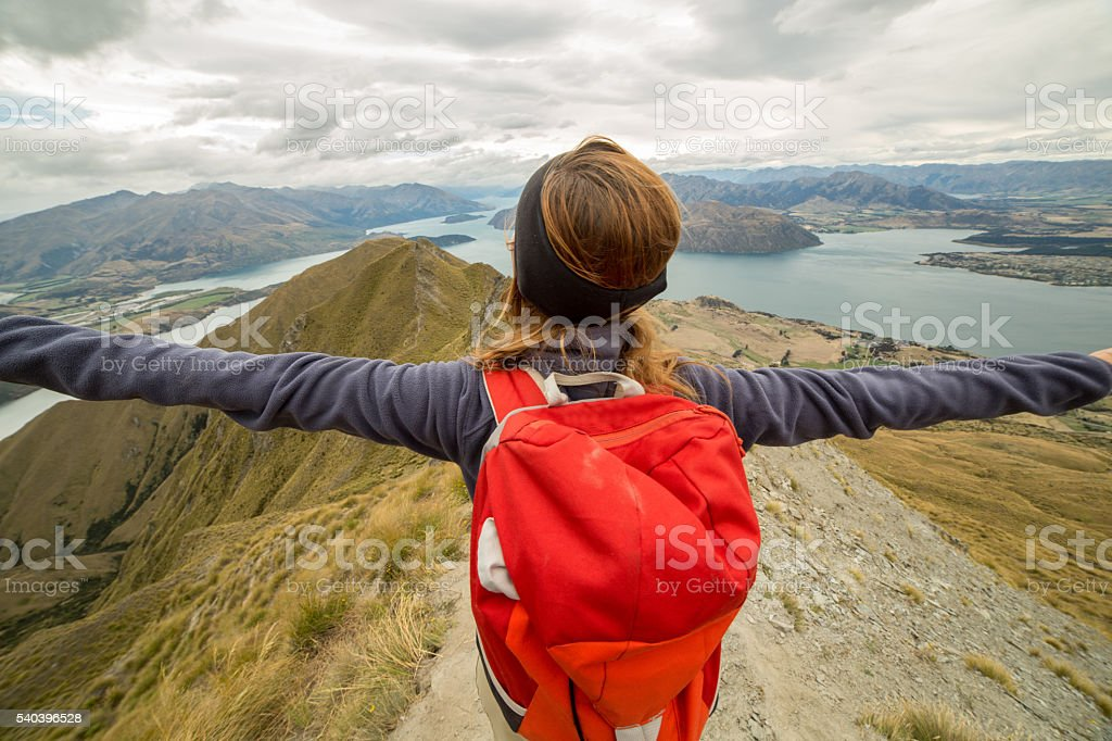 Young hiker woman standing on a mountain top arms outstretched for...