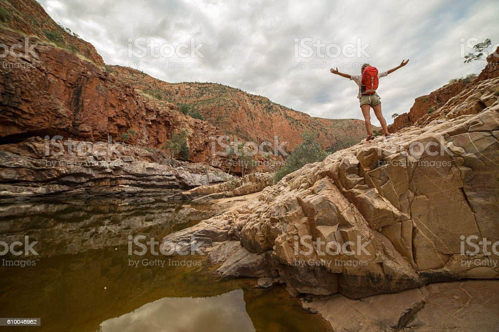 Caucasian female hiking in the Australia\'s outback stands arms...