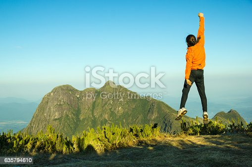 istock hiker celebrating success on top of a mountain 635794610