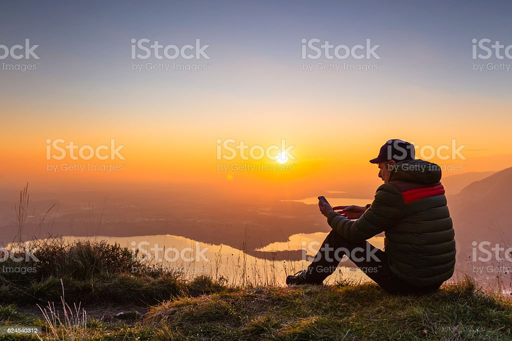 Hiker checks smartphone on top of the mountain during sunset stock photo
