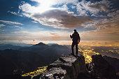 Hiker on top on the mount, full moon and city illuminated