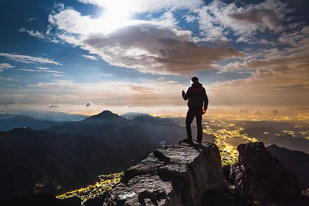 Hiker checks your device on top on the mount - foto de acervo