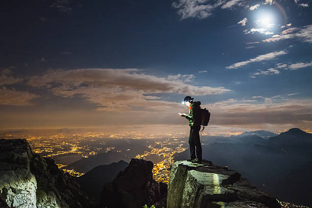 hiker checks your device on top on the mount - extreme sports stock photos and pictures