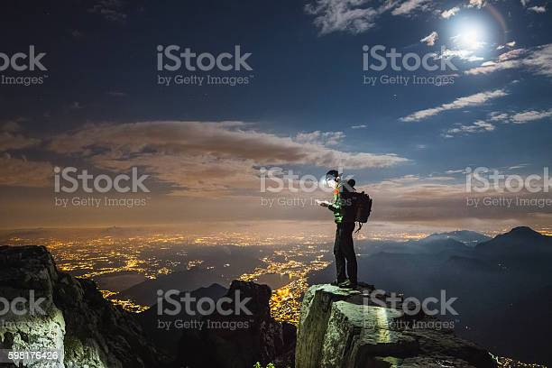 Photo of Hiker checks your device on top on the mount