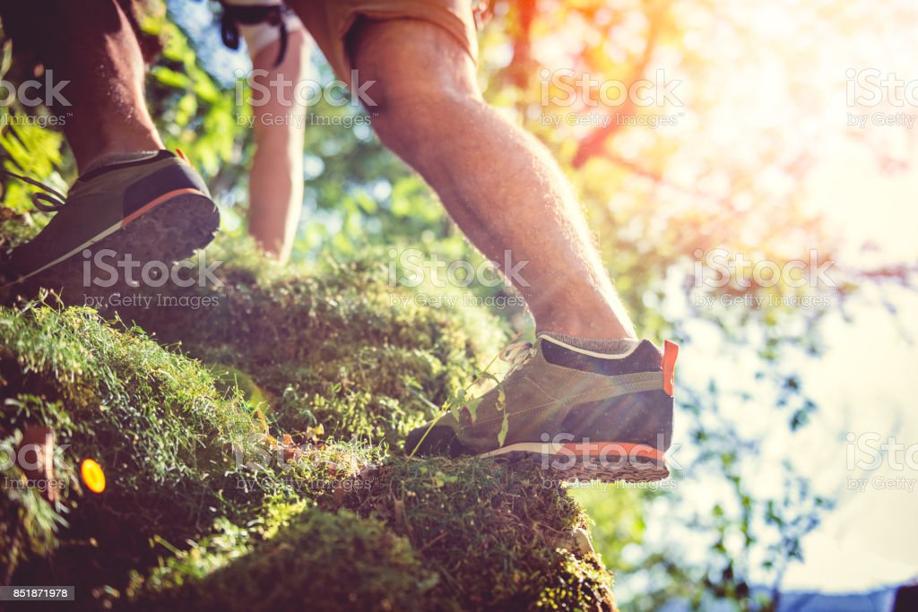 Hiker climbing on rock stock photo