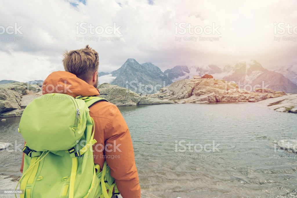 Hiker contemplating beautiful mountain view from trail, Switzerland stock photo