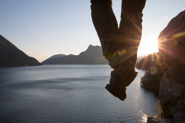 Hiker dangles legs above lake surface stock photo