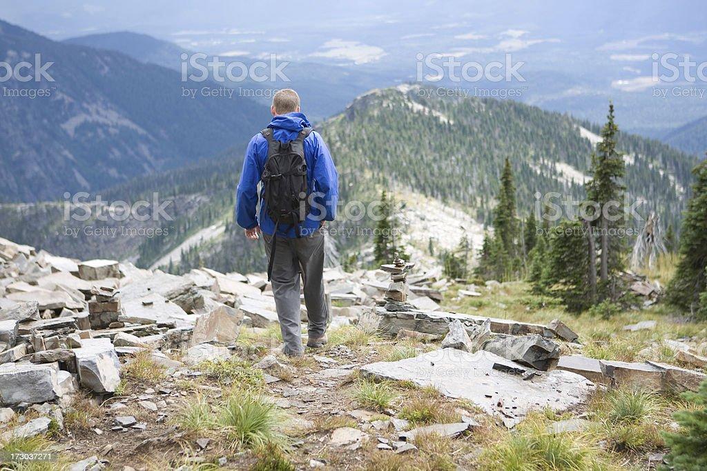 Hiker descending a trail above treeline stock photo