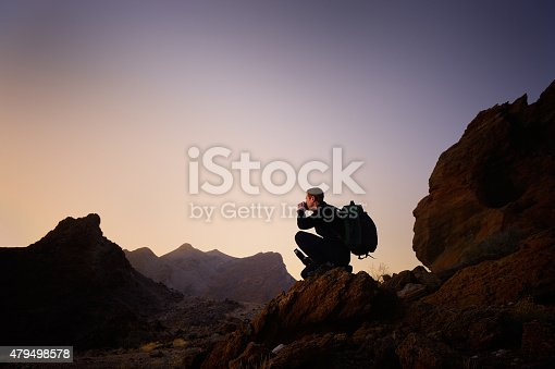 A man watching a sunrise over desert landscape at the border area between Namibia and South Africa. He is kneeling and drinking a hot beverage from a thermos flask, and carries a backpack.
