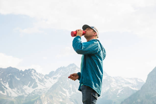 hiker drinking water in mountains - courmayeur estate foto e immagini stock