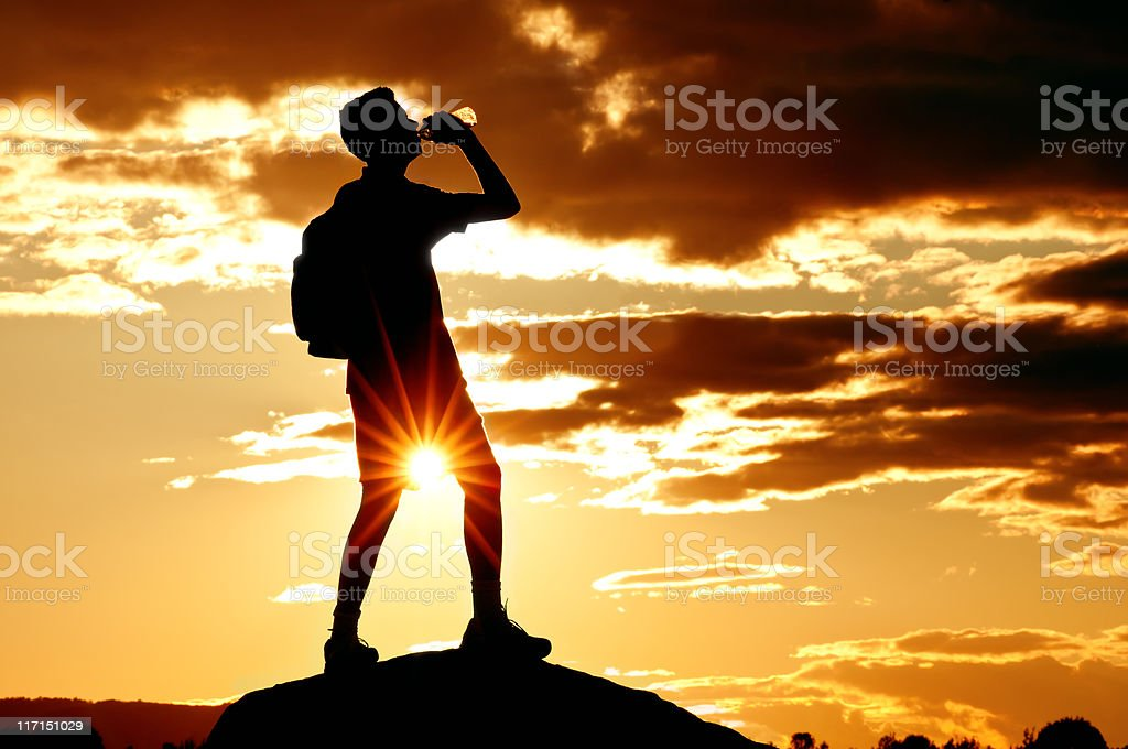 Hiker drinking water in the dramatic sunset - I royalty-free stock photo