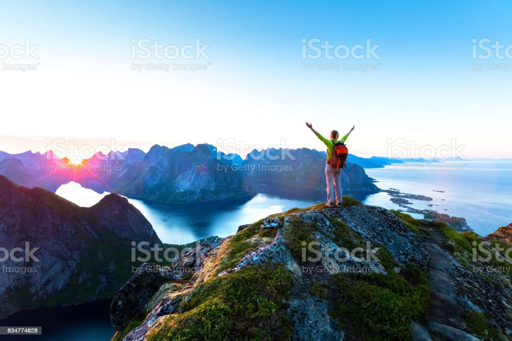 Hiker enjoying midnight sun during arctic summer, Reine, Lofoten, Norway stock photo