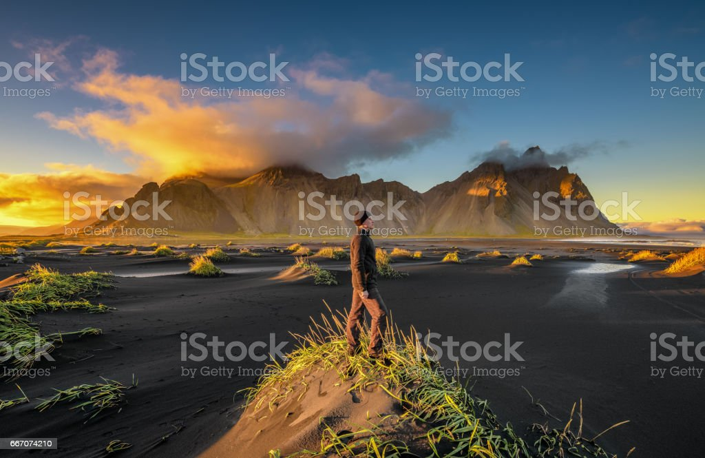 Hiker enjoying sunset at Vestrahorn and its black sand beach in Iceland stock photo