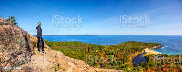Photo of Hiker enjoying the panoramic view from the top of Beehive Trail in Acadia