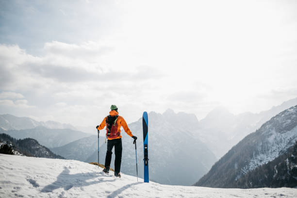 Hiker enjoying the views in the mountains before skiing back to the valley stock photo