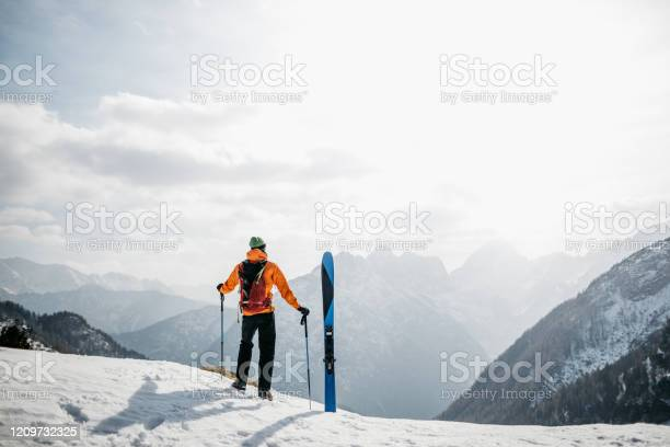 Photo of Hiker enjoying the views in the mountains before skiing back to the valley