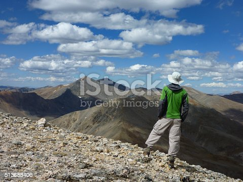 A hiker on the 13,794 foot on Square Top Mountain looks towards the Argentine Pass and the Continental Divide with Grays and Torreys Peaks standing tall on the horizon in the distance.