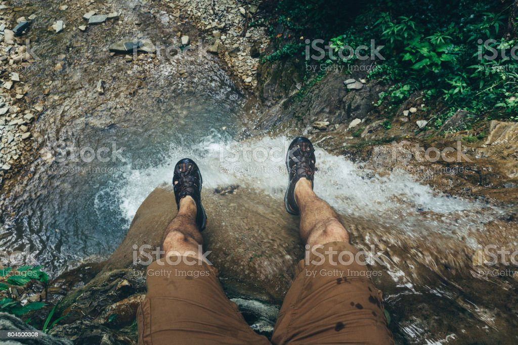 Hiker Explorer Sitting On Cliff With Waterfall View. Travel Lifestyle Adventure Vacations Concept stock photo