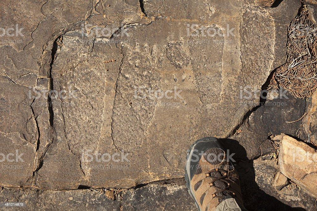 Hiker explores Native American foot petroglyphs Colorado royalty-free stock photo