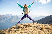 Hiker female celebrates success on mountain top