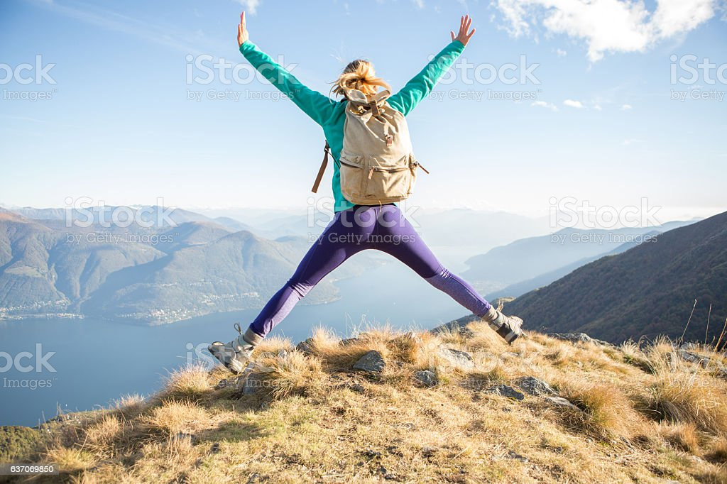 Hiker female celebrates success on mountain top stock photo