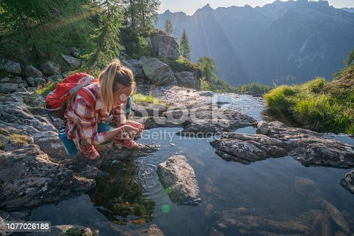 Young woman hiker on trail in Summer refreshing from water river Shot in Switzerland  People travel outdoor concept