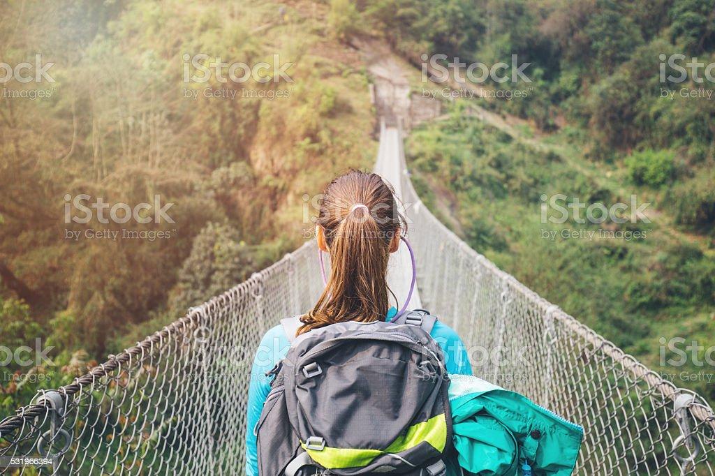 Hiker girl crossing footbridge stock photo