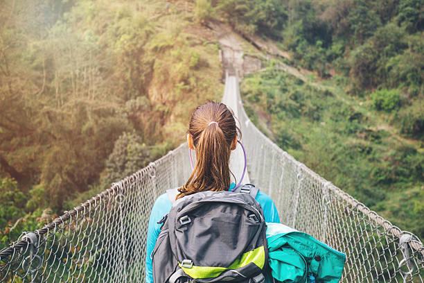 randonneur fille en traversant une passerelle - passerelle pont photos et images de collection