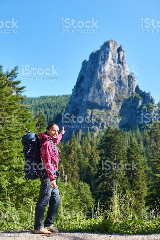 951fc4497b Hiker girl in modern outfit with blue backpack pointing with a hand on big  stone cliff. Young hiker woman in pink jacket and gray pants enjoying view  of ...