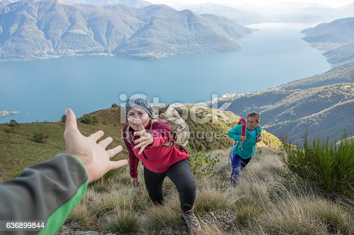 istock Hiker giving helping hand to teammate 636899844