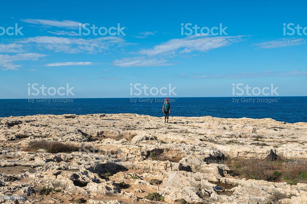 Hiker goes along rocky coast of sea stock photo