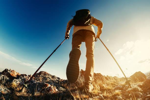 Hiker goes with trekking poles uphill