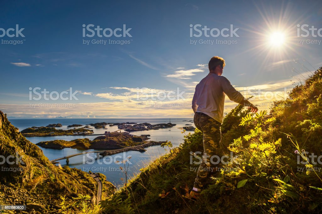 Hiker going to the top of mount Festvagtinden on Lofoten islands stock photo